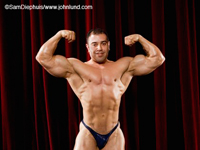 Handsome smiling body building contestant up on the stage flexing his biceps for the audience and judges. The man has short brown hair and is smiling at the camera. Big massive chest and back muscles. The man is wearing a thong.